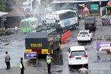Kendaraan polisi water Cannon menyemprotkan cairan disinfektan di pintu keluar Pelabuhan Ketapang, Banyuwangi, Jawa Timur, Minggu (27/12/2020). Kepala Korlantas menegaskan, pihaknya akan mengawasi ketat proses penerapan protokol kesehatan Covid-19 di setiap pos yang disinggahi masyarakat dalam merayakan libur Natal 2020 dan Tahun Baru 2021. Antara Jatim/Budi Candra Setya/Um