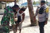 Babinsa-Bhabinkamtibmas bantu perbaiki mesin perahu warga di kampung Yenusi