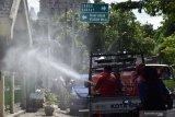 Petugas menyemprotkan cairan disinfektan di sebuah kawasan permukiman di Kota Madiun, Jawa Timur, Rabu (30/12/2020). Pemerintah setempat mengajak masyarakat meningkatkan kewaspadaan dan bersama-sama melakukan pencegahan penularan COVID-19 seiring terus meningkatnya kasus positif COVID-19 hingga daerah yang sebelumnya sempat berstatus zona hijau pertama di Jawa Timur tersebut kini berubah menjadi zona merah. Antara Jatim/Siswowidodo/Um