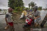 Sejumlah pengendara roda dua nekat menorobos banjir akibat luapan Sungai Martapura di Kabupaten Banjar, Kalimantan Selatan, Kamis (7/1/2021). Menurut warga setempat, banjir akibat luapan Sungai Martapura sudah berlangsung selama 15 hari merendam kawasan tersebut sehingga mengganggu aktivitas warga, dan hingga Kamis (7/1/2021) pemerintah daerah belum memberikan bantuan apapun. Foto Antaranews Kalsel/Bayu Pratama S.