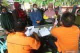 Warga terdampak pandemi COVID-19 mencairkan Bantuan Sosial Tunai (BST) di kantor Pos, Kota Kediri, Jawa Timur, Jumat (8/1/2020). Pemerintah menyiapkan anggaran sebesar Rp110 triliun pada tahun 2021 untuk bantuan sosial kepada masyarakt penerima manfaat di 34 provinsi guna membantu mengatasi dampak pandemi COVID-19 serta menggerakkan ekonomi nasional. Antara Jatim/Prasetia Fauzani/ZK