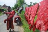 Pekerja menjemur batik setengah jadi di Desa Klampar, Pamekasan, Jawa Timur, Jumat (8/1/2021). Pengusaha batik daerah itu mulai meningkatkan penggunaan jasa travel dan jasa pengiriman lainnya guna memasarkan usahanya ke sejumlah daerah, menyusul akan diberlakukan Pembatasan Pergerakan Jawa-Bali atau Pelaksanaan Pembatasan Kegiatan Masyarakat (PPKM) pada 11-25 Januari. Antara Jatim/Saiful Bahri/Zk