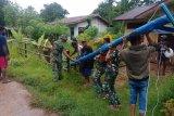 Satgas Pamtas Yonif 125 bersama warga perbatasan  Papua pasang tiang listrik