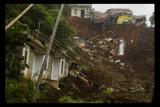 Kondisi permukiman dan tebing pascalongsor di Cimanggung, Kabupaten Sumedang, Jawa Barat, Minggu (10/1/2021). Tanah longsor yang diduga terjadi akibat intensitas curah hujan yang tinggi pada Sabtu (9/1) sore tersebut mengakibatkan 12 orang korban meninggal dua dan belasan orang diperkirakan masih tertimbun serta 14 bangunan rusak berat. ANTARA FOTO/Novrian Arbi/wsj.