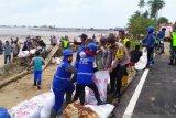 Polres  Natuna bersama TNI dan warga bangun  tanggul karena ombak besar
