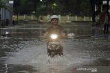 Pengendara motor melintasi genangan air di kawasan Tarogong Kidul, Kabupaten Garut, Jawa Barat, Rabu (13/1/2021). Hujan deras dan perbaikan drainase yang belum tuntas di kawasan tersebut mengakibatkan banjir menggenangi jalan setinggi 50 cm. ANTARA JABAR/Candra Yanuarsyah/agr