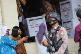 Personel Brimob berjaga saat proses bongkar muatan mobil pendingin yang mengangkut vaksin COVID-19 Sinovac di Gudang Farmasi Dinas Kesehatan Kota Surabaya, Surabaya, Jawa Timur, Rabu (13/1/2021). Dinas Kesehatan Provinsi Jawa Timur mulai mendistribusikan vaksin COVID-19 Sinovac ke Surabaya sebanyak 15.000 dosis, Kabupaten Sidoarjo sebanyak 4.000 dosis dan Kabupaten Gresik sebanyak 3.000 dosis. Antara Jatim/Didik/Zk