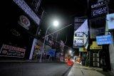Suasana kawasan wisata Jalan Legian tampak sepi saat penerapan Pemberlakuan Pembatasan Kegiatan Masyarakat (PPKM) di Kuta, Badung, Bali, Selasa (12/1/2021). Seluruh kegiatan usaha di kawasan tersebut dibatasi operasionalnya hingga pukul 21.00 WITA saat penerapan kebijakan PPKM sebagai upaya untuk menekan penyebaran COVID-19. ANTARA FOTO/Fikri Yusuf/nym.