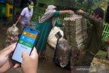 Relawan memasukkan data sampah melalui aplikasi Sistem Informasi Bank Sampah (SIBK) usai ditimbang di Bank Sampah LATANZA binaan PT Pupuk Kujang, Desa Cikampek Barat, Karawang, Jawa Barat, Rabu (13/1/2021). Aplikasi tersebut untuk mempermudah keterbukaan administrasi penimbangan sampah bagi masyarakat dan juga dapat digunakan sebagai pembayaran pajak, pembelian token listrik, pembukaan rekening dan tabungan emas Antam berbayar sampah. ANTARA JABAR/M Ibnu Chazar/agr