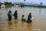 Sejumlah warga berjalan menerobos banjir di Desa Tanjungsari, Kecamatan Sukaresik, Kabupaten Tasikmalaya, Jawa Barat, Kamis (14/1/2021). Akibat intensitas hujan yang tinggi, luapan air Sungai Citanduy dan Cikidang meluas hingga merendam 400 rumah warga di Dusun Bojongsoban dan Hegarsari dengan ketinggian mencapai sekitar 80 sentimeter hingga 1,5 meter. ANTARA JABAR/Adeng Bustomi/agr