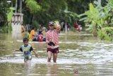 Warga berjalan menerobos banjir di Desa Tanjungsari, Kecamatan Sukaresik, Kabupaten Tasikmalaya, Jawa Barat, Kamis (14/1/2021). Akibat intensitas hujan yang tinggi, luapan air Sungai Citanduy dan Cikidang meluas hingga merendam 400 rumah warga di Dusun Bojongsoban dan Hegarsari dengan ketinggian mencapai sekitar 80 sentimeter hingga 1,5 meter. ANTARA JABAR/Adeng Bustomi/agr