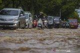Sejumlah pengendara sepeda motor menorobos banjir yang menggenangi jalan Brigjend H Hasan Basry di Banjarmasin, Kalimantan Selatan, Kamis (14/1/2021). Tingginya intensitas curah hujan mengakibatkan sejumlah kawasan di Kota Banjarmasin terendam banjir. Foto Antaranews Kalsel/Bayu Pratama S.