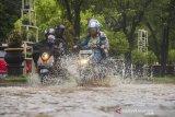 Sejumlah pengendara sepeda motor menorobos banjir yang menggenangi jalan Brigjend Hasan Basry di Banjarmasin, Kalimantan Selatan, Kamis (14/1/2021). Tingginya intensitas curah hujan mengakibatkan sejumlah kawasan di Kota Banjarmasin terendam banjir. Foto Antaranews Kalsel/Bayu Pratama S.