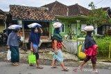 Warga membawa pulang bantuan sosial non tunai di Desa Tanjungsari, Kecamatan Sukaresik, Kabupaten Tasikmalaya, Jawa Barat, Kamis (14/1/2021). Sebanyak 7.421.816 Keluarga Penerima Manfaat (KPM) di Provinsi Jawa Barat mendapat bantuan tunai dari Pemerintah Pusat yang terdiri dari Program Keluarga Harapan (PKH), Bantuan Pangan Non Tunai (BPNT)/Program Sembako dan Bantuan Sosial Tunai (BST). ANTARA JABAR/Adeng Bustomi/agr