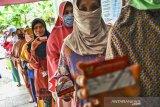 Sejumlah warga mengatre saat pencairan bantuan sosial non tunai di Desa Tanjungsari, Kecamatan Sukaresik, Kabupaten Tasikmalaya, Jawa Barat, Kamis (14/1/2021). Sebanyak 7.421.816 Keluarga Penerima Manfaat (KPM) di Provinsi Jawa Barat mendapat bantuan tunai dari Pemerintah Pusat yang terdiri dari Program Keluarga Harapan (PKH), Bantuan Pangan Non Tunai (BPNT)/Program Sembako dan Bantuan Sosial Tunai (BST). ANTARA JABAR/Adeng Bustomi/agr