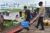 Petugas kesehatan (tengah) dikawal personil Polri dan TNI membawa kotak obat berisi vaksin COVID-19 Sinovac saat menumpang kapal penyeberangan tujuan wilayah terluar Pulau Aceh, di pelabuhan tradisional Lampulo, Banda Aceh, Aceh, Sabtu (16/1/2021). Sasaran vaksinasi tenaga kesehatan di provinsi Aceh tersebut mencapai 56.450 orang dan sebanyak 46 orang di antara berada di wilayah terluar Pulau Aceh.  Antara Aceh/Ampelsa.