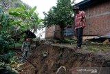 Warga mengamati lokasi tanah yang amblas akibat bencana tanah bergerak di Desa Lamkleng Kecamatan Cot Glie, Aceh Besar, Aceh, Sabtu (16/1/2021). Bencana yang menyebabkan amblasnya tanah sepanjang ratusan meter dengan kedalaman lebih dari satu meter di pinggiran Krueng (sungai) Aceh itu mengancam 15 unit rumah warga. Antara Aceh/Irwansyah Putra.