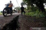 Warga melintas di jalan yang retak akibat bencana tanah bergerak di Desa Lamkleng Kecamatan Cot Glie, Aceh Besar, Aceh, Sabtu (16/1/2021). Bencana yang menyebabkan amblasnya tanah sepanjang ratusan meter dengan kedalaman lebih dari satu meter di pinggiran Krueng (sungai) Aceh itu mengancam 15 unit rumah warga dan jalan desa. Antara Foto/Irwansyah Putra.