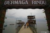 Pengunjung melintas di jembatan saat berlibur di kawasan wisata Dermaga Rindu di Bangkalan, Jawa Timur, Sabtu (16/1/2021). Tempat wisata berkonsep resto dan kafe dengan pemandangan Jembatan Suramadu tersebut menjadi salah satu destinasi wisata yang dikunjungi banyak wisatawan saat berlibur ke Pulau Madura. Antara Jatim/Moch Asim/ZK