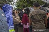 Presiden Joko Widodo (tengah) memberikan bingkisan kepada anak-anak saat meninjau banjir di Desa Pekauman Ulu, Kabupaten banjar, Kalimantan Selatan, Senin (18/1/2021). Kunjungan kerja tersebut dalam rangka melihat langsung dampak banjir dan meninjau posko pengungsian korban banjir di Provinsi Kalimantan Selatan. Foto Antaranews Kalsel/Bayu Pratama S.