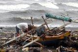 Seorang nelayan memeriksa perahunya yang rusak terhempas ombak di pesisir pantai di Manado, Sulawesi Utara, Senin (18/1/2021). Ombak setinggi empat meter yang menerjang pesisir pantai Manado membawa tumpukan sampah serta merusak sejumlah lapak dan bangunan semi permanen milik warga. ANTARA FOTO/Adwit B Pramono/nym.