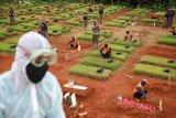 Sejumlah pelanggar protokol kesehatan COVID-19 berdoa saat penerapan sanksi di TPU Jombang, Kota Tangerang Selatan, Banten, Senin (18/1/2021). Pemerintah Kota Tangerang Selatan menerapkan sanksi bagi para pelanggar protokol kesehatan COVID-19 yaitu dengan mengajak mereka berdoa di makam khusus COVID-19 guna menimbulkan efek jera dengan melihat langsung proses pemakaman dan makam para korban yang meninggal akibat terpapar COVID-19. ANTARA FOTO/Fauzan/nym.