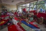 Sejumlah pengungsi korban banjir beristirahat di posko pengungsian korban banjir di Stadion Demang Lehman, Martapura, Kabupaten Banjar, Kalimantan Selatan, Selasa (19/1/2021). Berdasarkan data relawan Posko Pengungsian Korban Banjir Stadion Demang Lehman dari Rabu (13/1/2021) hingga Selasa (19/1/2021) sebanyak 860 warga yang terdampak banjir di Kalimantan Selatan mengungsi di Stadion tersebut. Foto Antaranews Kalsel/Bayu Pratama S.