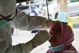 Petugas kesehatan mengambil sampel dahak seorang warga saat tes usap (swab) massal di halaman Wisma Haji Kota Madiun, Jawa Timur, Selasa (19/1/2021). Pemkot Madiun memfasilitasi swab secara gratis bagi warga yang memiliki riwayat kontak erat dengan pasien positif COVID-19 guna pencegahan penyebaran virus corona seiring dengan terus meningkatnya jumlah kasus positif COVID-19 hingga daerah tersebut berstatus zona merah COVID-19. Antara Jatim/Siswowidodo/ZK
