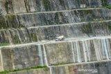 Truk melintas di tebing pembangunan Bendungan Leuwi Keris di Kabupaten Tasikmalaya, Jawa Barat, Rabu (20/1/2021). Proyek pembangunan Bendungan Leuwi Keris yang mampu menampung 81,44 juta meter kubik air sebagai sumber irigasi dan Pembangkit Listrik Tenaga Air (PLTA) tersebut sudah mencapai 59,49 persen dengan target selesai pada tahun 2023 mendatang. ANTARA JABAR/Adeng Bustomi/agr
