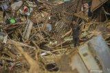 Seorang warga berada di puing-puing rumah akibat banjir bandang di Desa Waki, Kecamatan Batu Benawa,Kabupaten Hulu Sungai Tengah, Kalimantan Selatan, Kamis (21/1/2021). Berdasarkan data bencana alam banjir Badan Penanggulangan Bencana Daerah (BPBD) Kabupaten Hulu Sungai Tengah pada Selasa (18/1/2021) sebanyak 57.624 jiwa terdampak banjir serta sembilan jiwa dinyatakan meninggal dunia dan enam jiwa hilang. Foto Antaranews Kalsel/Bayu Pratama S.