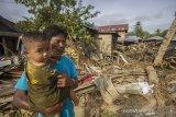 Warga melintas di dekat puing-puing rumah akibat banjir bandang di Desa Waki, Kecamatan Batu Benawa,Kabupaten Hulu Sungai Tengah, Kalimantan Selatan,Kamis (21/1/2021). Berdasarkan data bencana alam banjir Badan Penanggulangan Bencana Daerah (BPBD) Kabupaten Hulu Sungai Tengah pada Selasa (18/1/2021) sebanyak 57.624 jiwa terdampak banjir serta sembilan jiwa dinyatakan meninggal dunia dan enam jiwa hilang. Foto Antaranews Kalsel/Bayu Pratama S.