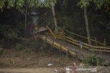 Seorang anak bermain di jembatan rusak akibat banjir bandang di Desa Waki, Kabupaten Hulu Sungai Tengah, Kalimantan Selatan, Kamis (21/1/2021). Berdasarkan data Badan Penanggulangan Bencana Daerah (BPBD) Provinsi Kalsel pada Rabu (20/1/2021) sebanyak 21 Jembatan, 110 tempat ibadah, 76 sekolah serta 18.294 meter jalan terdampak banjir dan longsor di Kalimantan Selatan. Foto Antaranews Kalsel/Bayu Pratama S.