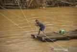 Seorang warga menyeberang sungai menggunakan tali akibat jembatan rusak diterjang banjir bandang di Desa Waki, Kabupaten Hulu Sungai Tengah, Kalimantan Selatan,Kamis (21/1/2021). Berdasarkan data Badan Penanggulangan Bencana Daerah (BPBD) Provinsi Kalsel pada Rabu (20/1/2021) sebanyak 21 Jembatan, 110 tempat ibadah, 76 sekolah serta 18.294 meter jalan terdampak banjir dan longsor di Kalimantan Selatan. Foto Antaranews Kalsel/Bayu Pratama S.