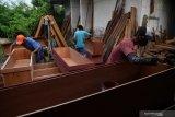 Pekerja menyelesaikan pembuatan peti jenazah COVID-19 di Surabaya, Jawa Timur, Kamis (21/1/2021). Perajin tersebut mengirim sedikitnya 12 peti mati untuk salah satu rumah sakit rujukan COVID-19 di Surabaya dan menyelesaikan sekitar 30 peti dalam sehari. Antara Jatim/Zabur Karuru