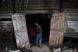 Pekerja memasukan  peti jenazah COVID-19 ke dalam gudang sebelum dikirim di Surabaya, Jawa Timur, Kamis (21/1/2021). Perajin tersebut mengirim sedikitnya 12 peti mati untuk salah satu rumah sakit rujukan COVID-19 di Surabaya dan menyelesaikan sekitar 30 peti dalam sehari. Antara Jatim/Zabur Karuru