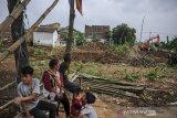 Warga menyaksikan alat berat yang menyelesaikan proyek pembangunan kolam retensi di Andir, Baleendah, Kabupaten Bandung, Jawa Barat, Kamis (21/1/2021). Kolam Retensi Andir dengan luas kurang lebih lima hektar  yang berfungsi untuk pengendali banjir luapan Sungai Citarum tersebut ditargetkan rampung pada akhir 2021 mendatang. ANTARA JABAR/Raisan Al Farisi/agr