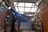 Warga melihat kondisi atap rumah kos yang rusak akibat diterpa angin puting beliung di Desa Pecatu, Badung, Bali, Kamis (21/1/2021). Angin puting beliung yang terjadi disaat hujan deras sekitar pukul 06.00 WITA tersebut merusak puluhan atap rumah kos dan warung serta tidak ada korban jiwa ataupun luka-luka dalam kejadian itu. ANTARA FOTO/Nyoman Hendra Wibowo/nym.