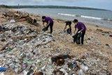 Sejumlah relawan membersihkan sampah yang terdampar di Pantai Kedonganan, Badung, Bali, Kamis (21/1/2021). Sampah kiriman akibat cuaca ekstrim itu terus memenuhi kawasan pantai di Kabupaten Badung tersebut dan dibersihkan secara bertahap. ANTARA FOTO/Nyoman Hendra Wibowo/nym.