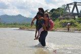 Warga menggendong anaknya saat menyeberangi sungai sepulang sekolah di wilayah pedalaman desa Panca, Kecamatan Lembah Seulawah, Kabupaten Aceh Besar, Aceh, Jumat, (22/1/2021). Menurut aparat desa, sejak tahun 2004 setelah putusnya jembatan gantung dan kemudian tahun 2008 dibangun jembatan konstruksi beton rangka baja yang hingga saat ini tidak tuntas pembangunannya, anak sekolah dan warga terpaksa menyeberangi sungai dan jika musim penghujan air sungai deras aktivitas belajar lumpuh dan begitu juga pemasaran komoditas pertanian ke ibu kota provinsi Aceh terhenti karena tidak ada jalan alternatif lainnya. ANTARA FOTO/Ampelsa.