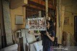 Seniman Ahmad Mufid Sururi (46) menunjukan wayang beber yang terbuat dari kulit kayu pohon paper mulberry (Broussonetia Papyryfera Vent) di Ujung Berung, Bandung, Jawa Barat, Jumat (22/1/2021). Ahmad Mufid Sururi berinisiatif untuk melestarikan daluang atau kertas tradisional Indonesia yang digunakan untuk menulis naskah dan menyungging wayang beber serta sebagai salah satu langkah mengenalkan tradisi pembuatan daluang kepada generasi berikutnya. ANTARA JABAR/Raisan Al Farisi/agr