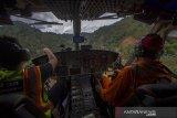 Pilot capt A Zaini dari Badan Nasional Penanggulangan Bencana (BNPB) menggunakan Helikopter jenis Bell 412 EP milik PT NUH melintasi lereng pegunungan meratus saat mengantarkan logistik bantuan korban banjir bandang di Desa Datar Ajab, Kabupaten Hulu Sungai Tengah, Kalimantan Selatan, Minggu (24/1/2021). Bantuan berupa tenda, sembako serta perlatan dapur dari TNI Angakatan Udara Lanud Sjamsudin Noor, Dharma Pertiwi Peduli, Kepala Staf Angkatan Udara dan Badan Penanggulangan Bencana Daerah (BPBD) Porvinsi Kalsel didistribusikan melalui jalur udara ke wilayah pedalaman pegunungan meratus. Foto Antaranews Kalsel/ Bayu Pratama S.