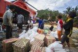 Sejumlah warga bersama petugas menurunkan logistik bantaun korban banjir bandang dari helikopter Badan Nasional Penanggulangan Bencana (BNPB) di Desa Datar Ajab, Kabupaten Hulu Sungai Tengah, Kalimantan Selatan, Minggu (24/1/2021). Bantuan berupa tenda, sembako serta perlatan dapur dari TNI Angakatan Udara Lanud Sjamsudin Noor, Dharma Pertiwi Peduli, Kepala Staf Angkatan Udara dan Badan Penanggulangan Bencana Daerah (BPBD) Porvinsi Kalsel didistribusikan melalui jalur udara ke wilayah pedalaman pegunungan meratus. Foto Antaranews Kalsel/ Bayu Pratama S.