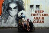 Warga negara asing melintas di dekat mural bergambar perempuan menggunakan masker di Badung, Bali, Minggu (24/1/2021). Jumlah kasus positif COVID-19 di Bali tetap tinggi saat Pemberlakuan Pembatasan Kegiatan Masyarakat (PPKM). ANTARA FOTO/Nyoman Hendra Wibowo/nym.