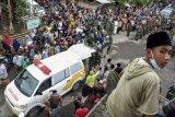 Ribuan warga turut mengantarkan jenazah Praka (Anumerta) Dedi Hamdani, anggota Yonif Raider 400/BR untuk dimakamkan di pemakaman Desa Pelambik, Kecamatan Praya Barat Daya, Lombok Tengah, NTB, Minggu (24/1/2021). Praka (Anumerta) Dedi Hamdani mendapatkan kehormatan kenaikan pangkat satu tingkat usai gugur akibat tertembak oleh kelompok kriminal bersenjata pada Jumat (22/1) saat melaksanakan tugas di Titigi Distrik Sugapa, Kabupaten Intan Jaya, Papua. ANTARA FOTO/Ahmad Subaidi/foc.