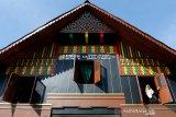 Warga melihat dari jendela rumah adat Aceh yang dibangun melalui program Kota Tanpa Kumuh (Kotaku) Kementerian Pekerjaan Umum dan Perumahan Rakyat di Desa Lambhuk, Banda Aceh, Aceh, Selasa (26/1/2021). Program Kotaku merupakan upaya pemerintah untuk mempercepat penanganan permukiman kumuh, mendukung gerakan 100 persen akses universal air minum, 0 persen permukiman kumuh dan 100 persen akses sanitasi layak (100-0-100). Antara Aceh/Irwansyah Putra.