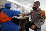 Kapolresta Kediri Eko Prasetyo (kanan) bersiap mengikuti vaksinasi saat pencanganan vaksinasi COVID-19 di Kota Kediri, Jawa Timur, Rabu (27/1/2021). Sebanyak 3.680 tenaga kesehatan di Kota Kediri akan divaksin pada tahap pertama di 6 rumah sakit dan 9 puskesmas. Antara Jatim/Prasetia Fauzani/zk.
