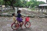 Dua orang anak bermain sepeda di tempat penambatan sapi di pasar hewan yang ditutup di Ngawi, Jawa Timur, Rabu (27/1/2021). Pemerintah setempat menutup sepuluh pasar hewan di kawasan tersebut guna mencegah makin meluasnya penyebaran COVID-19. Antara Jatim/Ari Bowo Sucipto/zk.