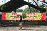 Seorang pencari rumput melintas di depan spanduk penutupan pasar hewan di Ngawi, Jawa Timur, Rabu (27/1/2021). Pemerintah setempat menutup sepuluh pasar hewan di kawasan tersebut guna mencegah makin meluasnya penyebaran COVID-19. Antara Jatim/Ari Bowo Sucipto/zk.