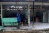 Seorang warga melintas di kios makanan di pasar hewan yang ditutup di Ngawi, Jawa Timur, Rabu (27/1/2021). Pemerintah setempat menutup sepuluh pasar hewan di kawasan tersebut guna mencegah makin meluasnya penyebaran COVID-19. Antara Jatim/Ari Bowo Sucipto/zk.
