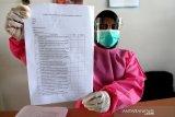 Petugas registrasi memperlihatkan formulir persyaratan untuk mendapatkan vaksinasi COVID-19 Sinovac bagi tenaga kesehatan di Puskesmas Ulee Kareng, Banda Aceh, Aceh, Rabu (27/1/2021). Menteri Kesehatan Budi Gunadi Sadikin menyebutkan terdapat 15 persen dari 1,48 juta tenaga kesehatan tahap pertama belum dapat diberikan vaksinasi COVID-19 karena terkendala tekanan darah tinggi dan memiliki penyakit penyerta (komorbid). Antara Aceh/Irwansyah Putra.